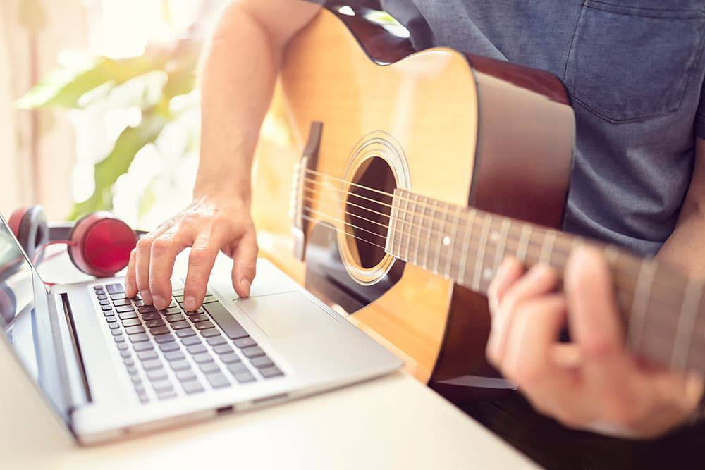 Adult playing guitar, taking online music lessons