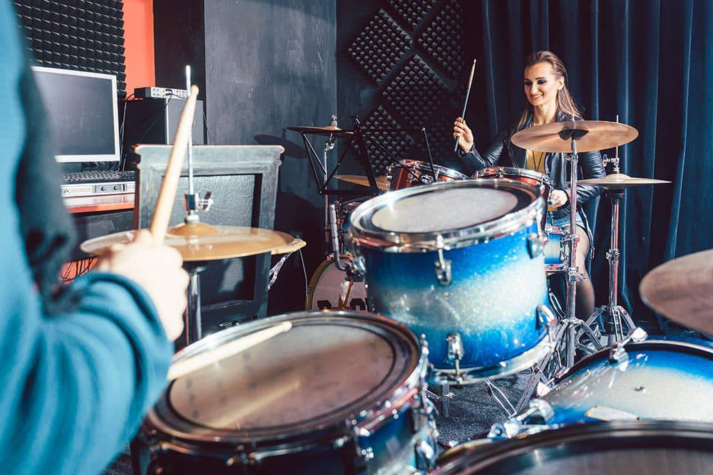 Adult woman learning to play drums in class