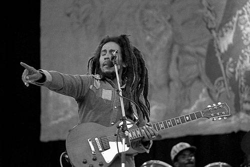 Bob Marley with guitar singing on stage