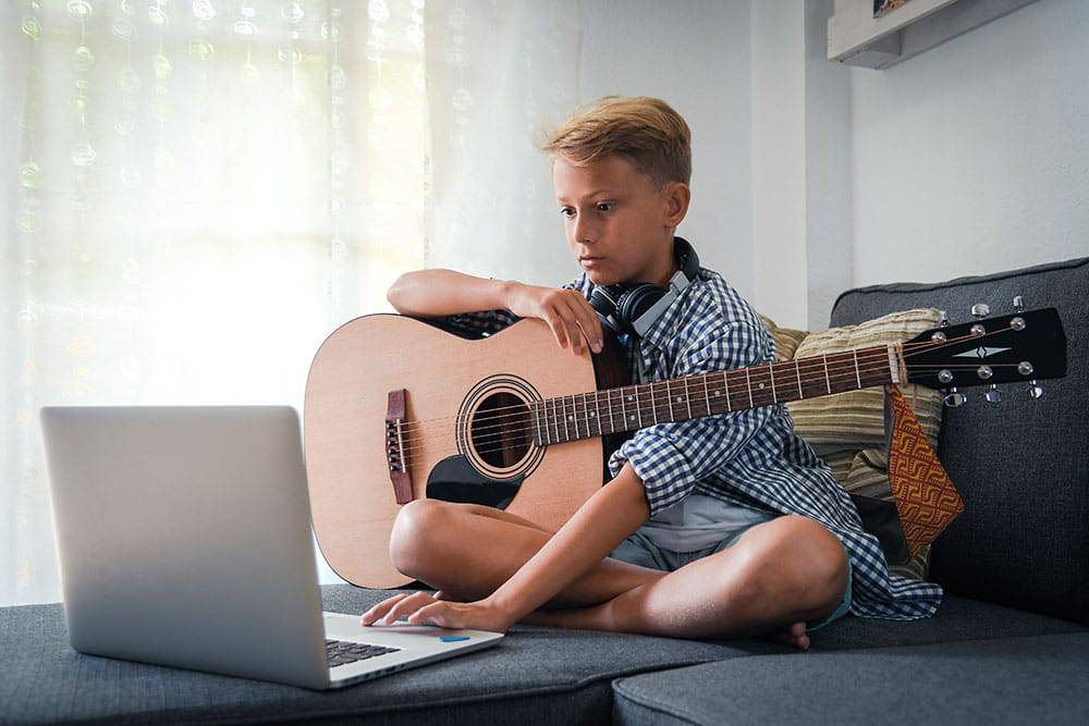 Boy sitting on bed in front of laptop holding guitar taking online guitar lessons