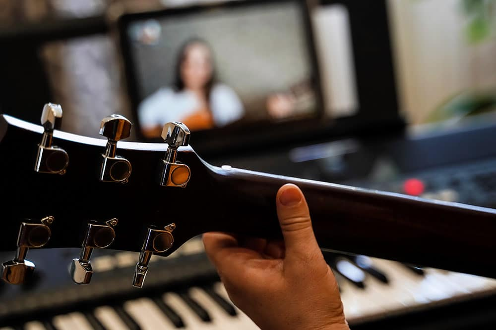 Close up of hand on guitar with laptop in background, taking online music lessons
