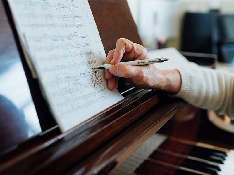 Close upof sheetof music someone writing music cover 1