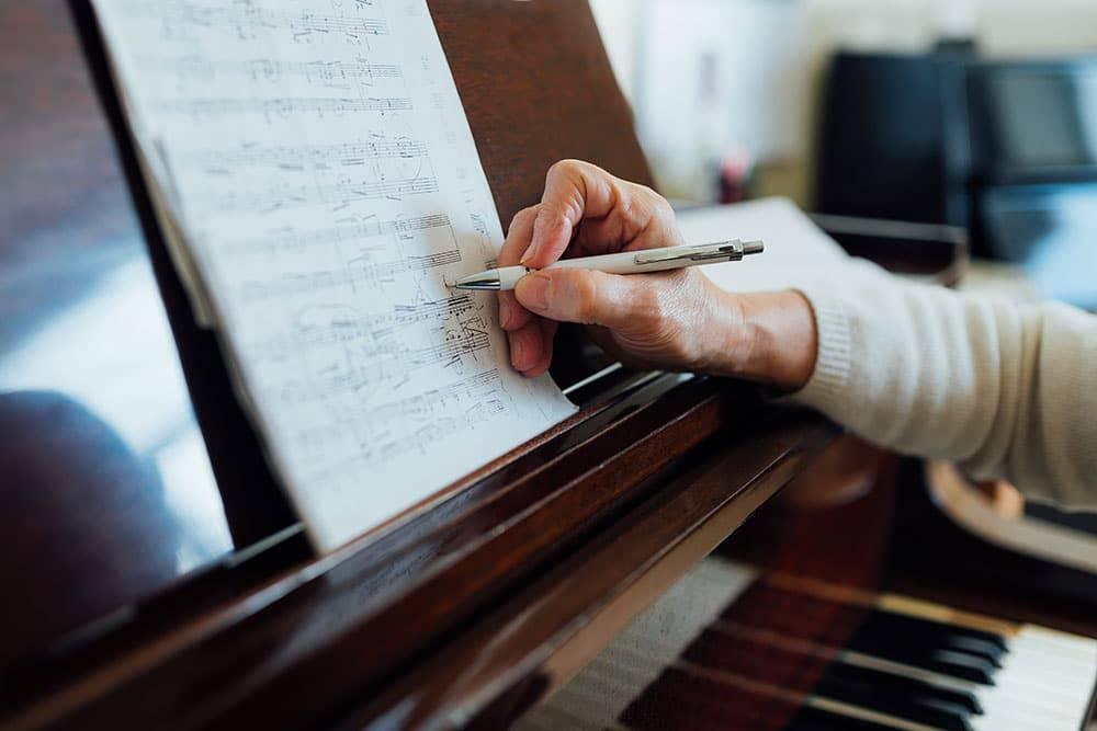 Close up of someone sitting at piano, writing music