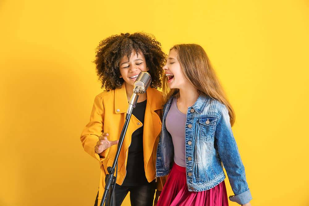 Two young girls singing into microphone in front of yellow background