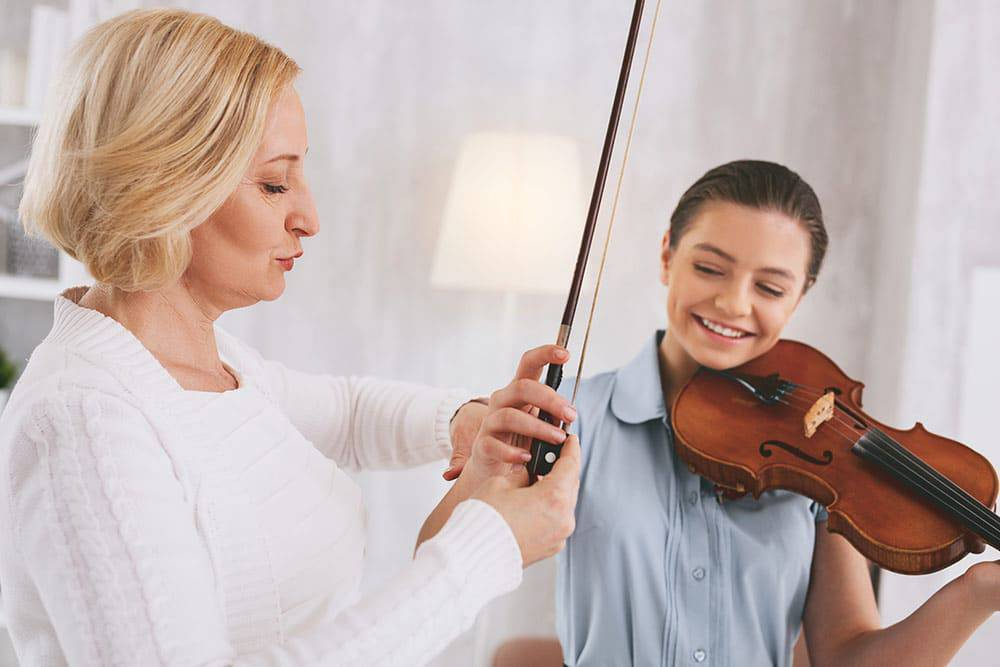 Instructor helping young girl with private music lessons in violin