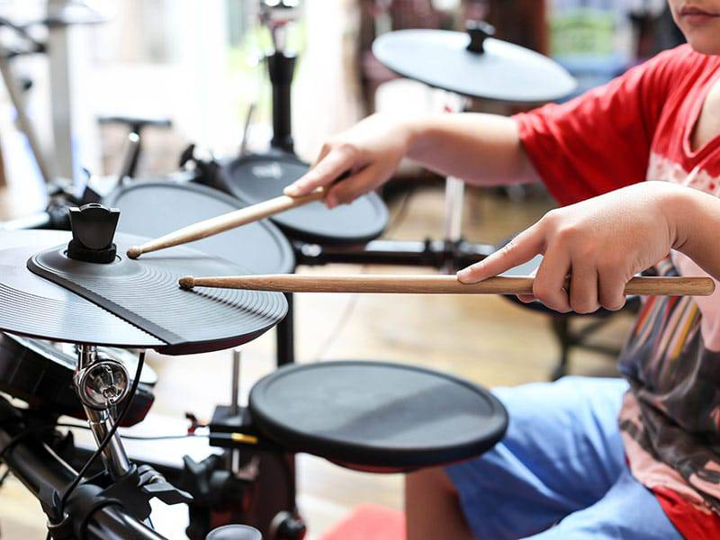 Kid hands playing drumswith sound pads cover