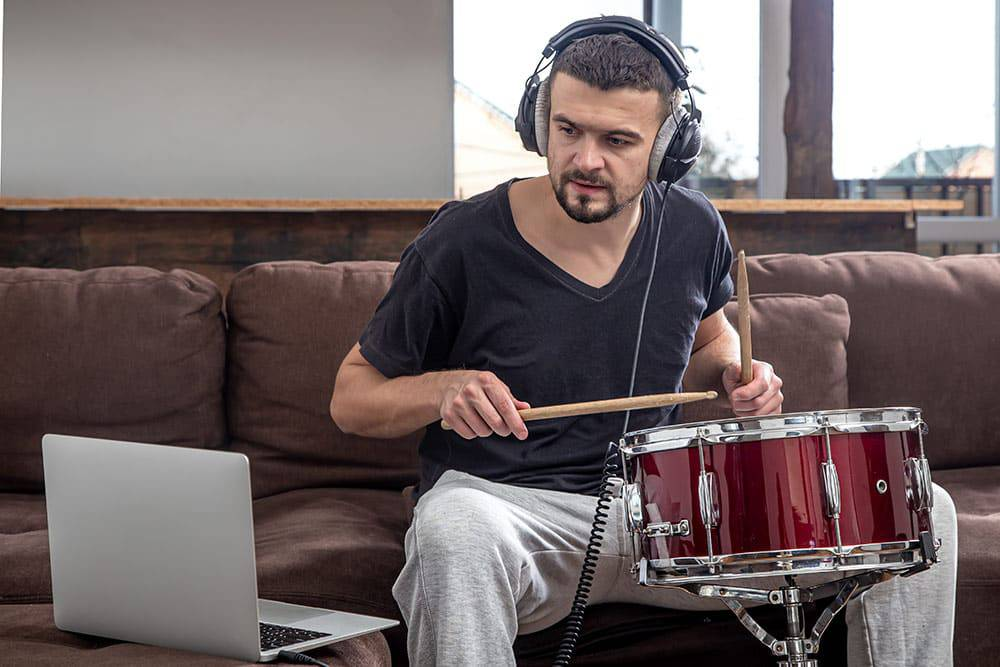 Man sitting on couch with headphones on, looking at laptop, and snare drum in front of him