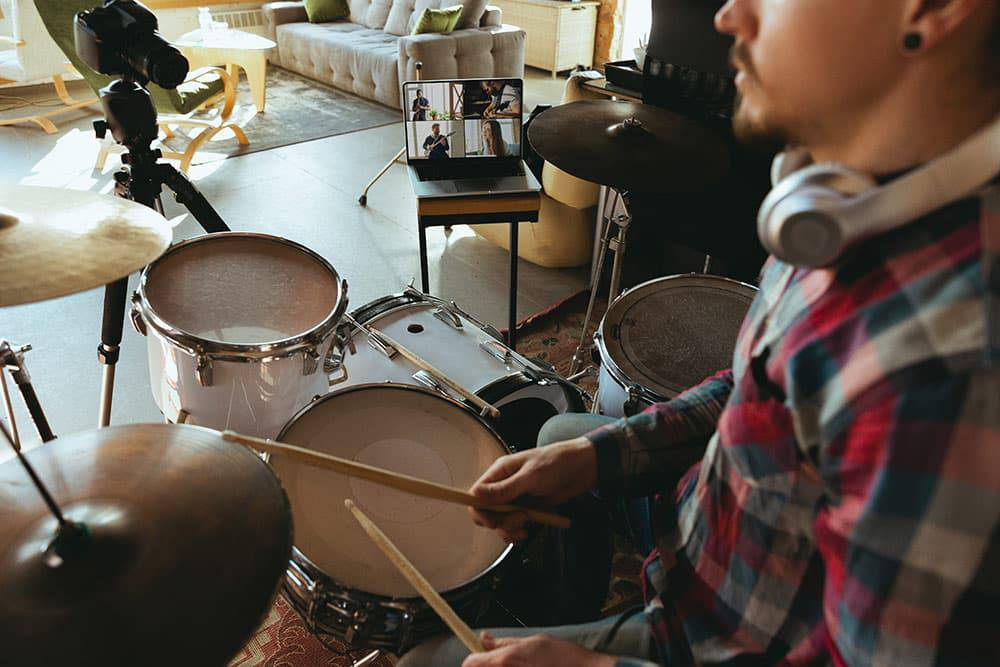 Man sitting at drum set with headphones on and looking at laptop, online music lessons