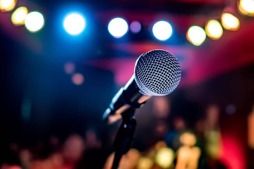 Close up of microphone on stand on stage with colorful lights in background