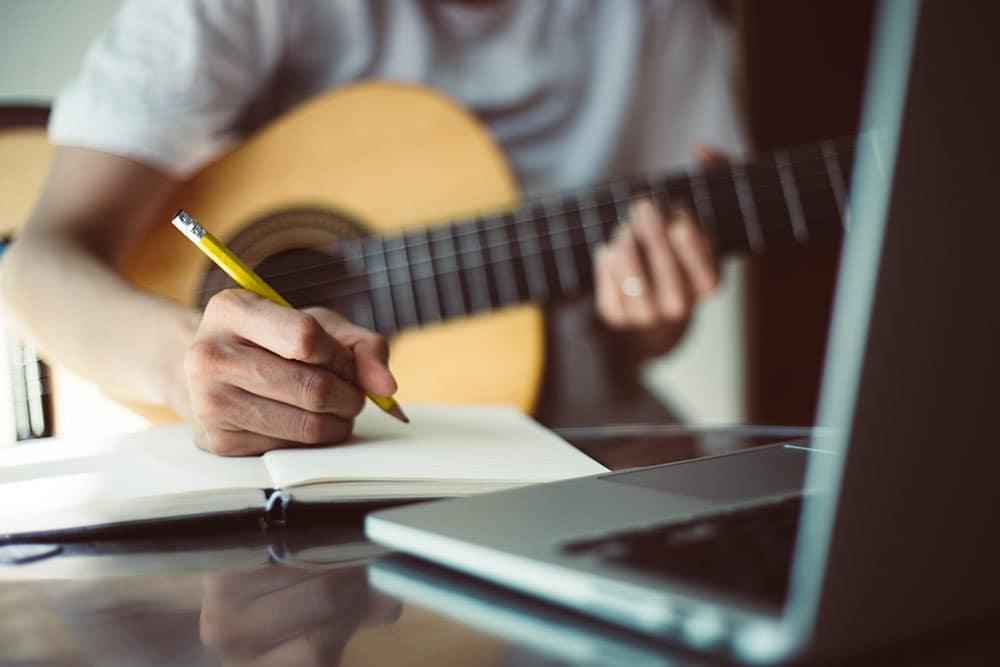 Close up of musician writing music with guitar in hand