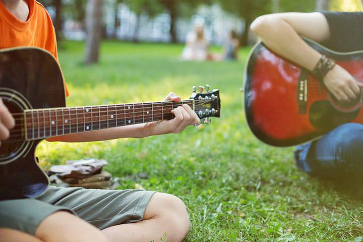 People playing guitar sitting in the grass at a park