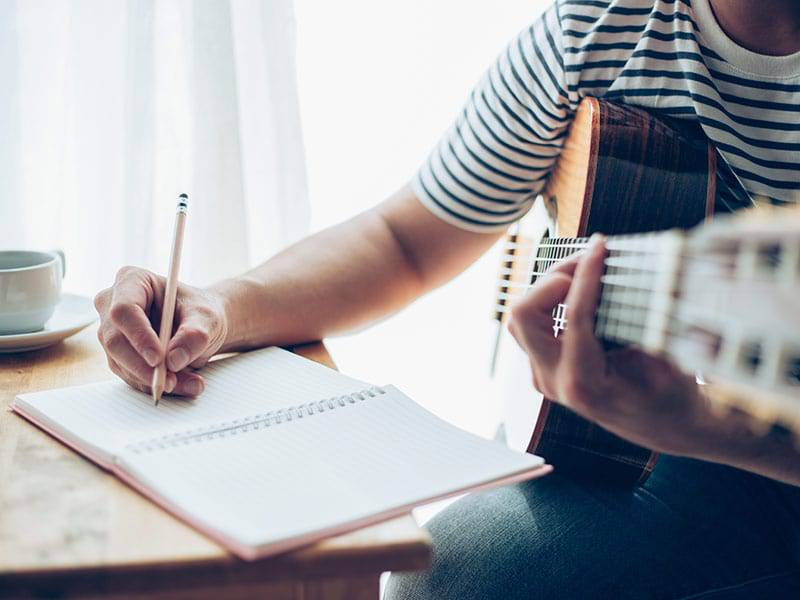 Person writing song with guitar cover image