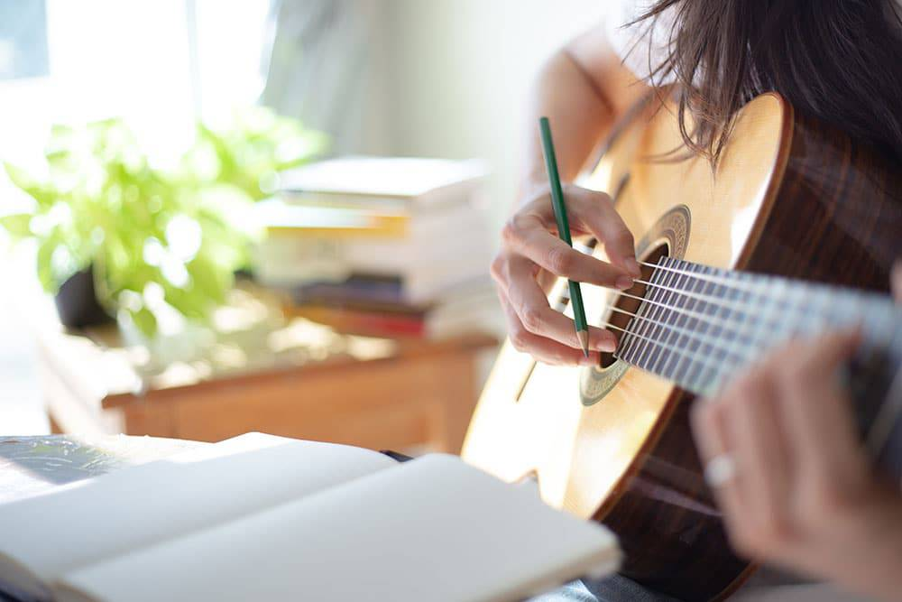Person holding guitar and writing music