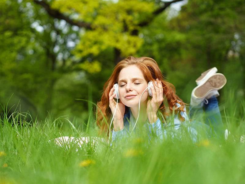 Red headed girl listening to music on headphones outside in grass cover