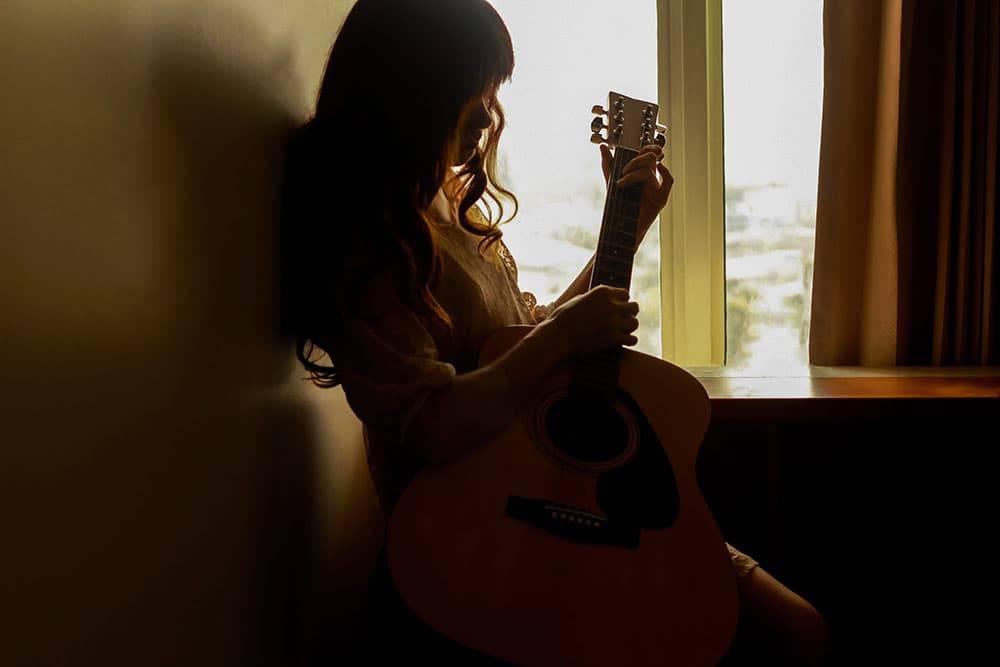 Sad girl with guitar sitting down in hallway
