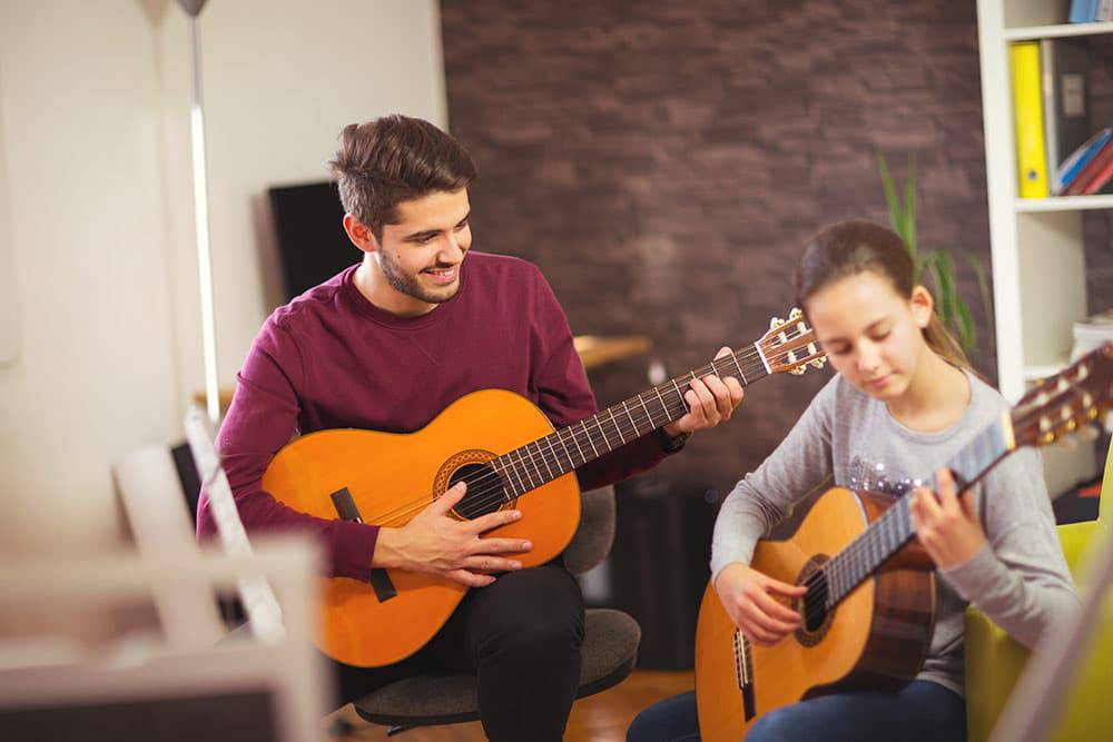 Student with instructor taking guitar lessons