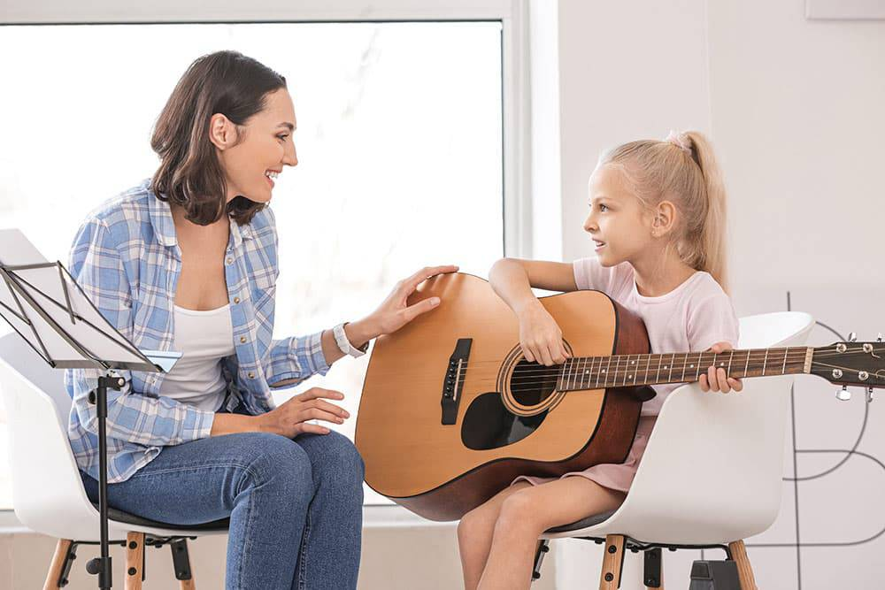 Teacher with young girl taking private music lessons with guitar