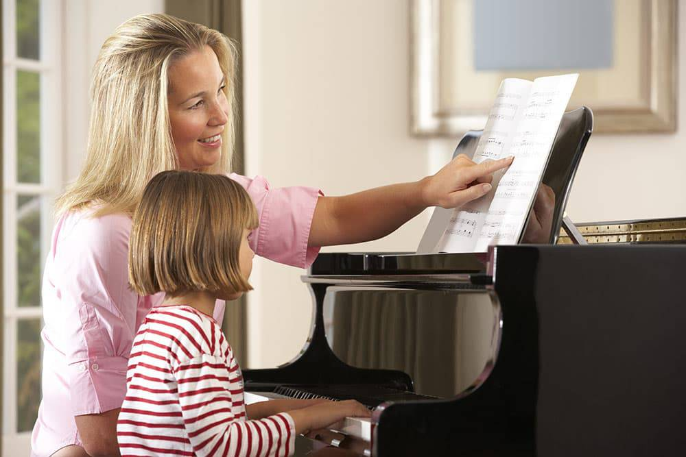 Teacher with young girl taking piano lessons