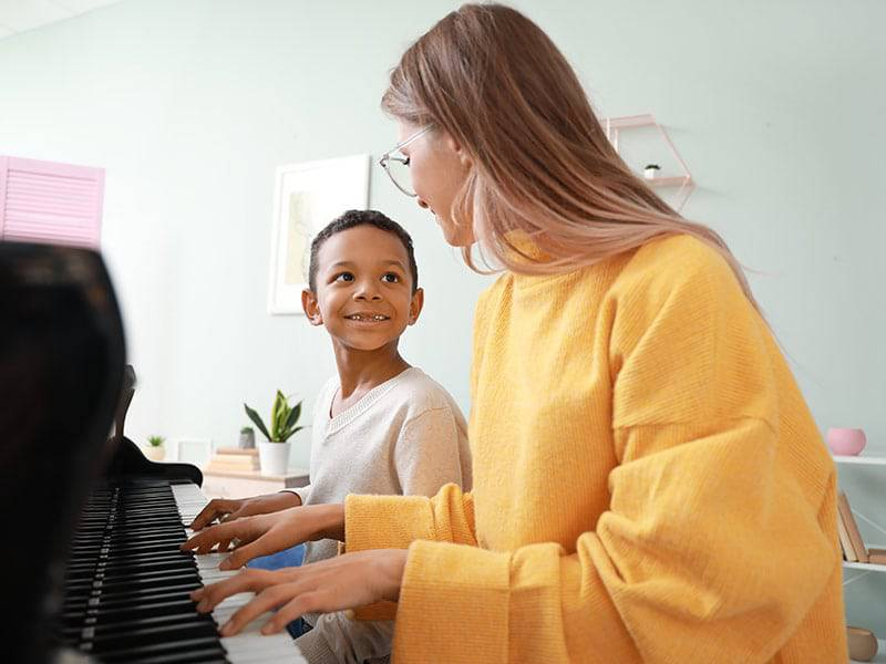Teacherwith young boy sittingat piano music lessons cover