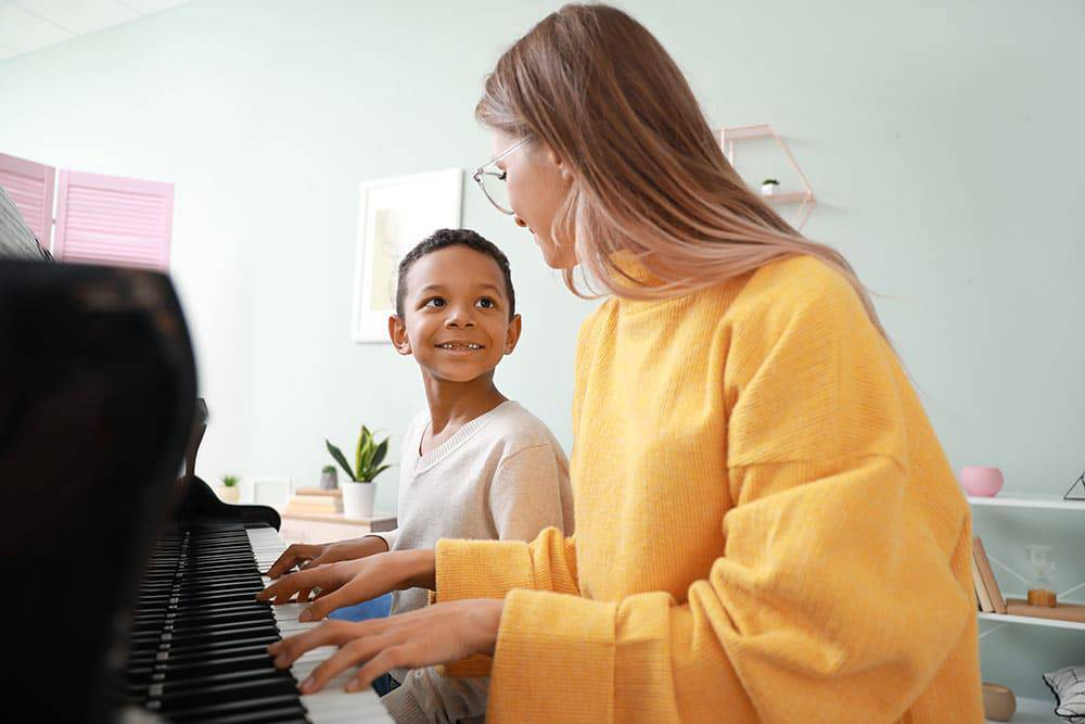 Young boy taking private music lessons in piano witting at the piano with instructor smiling