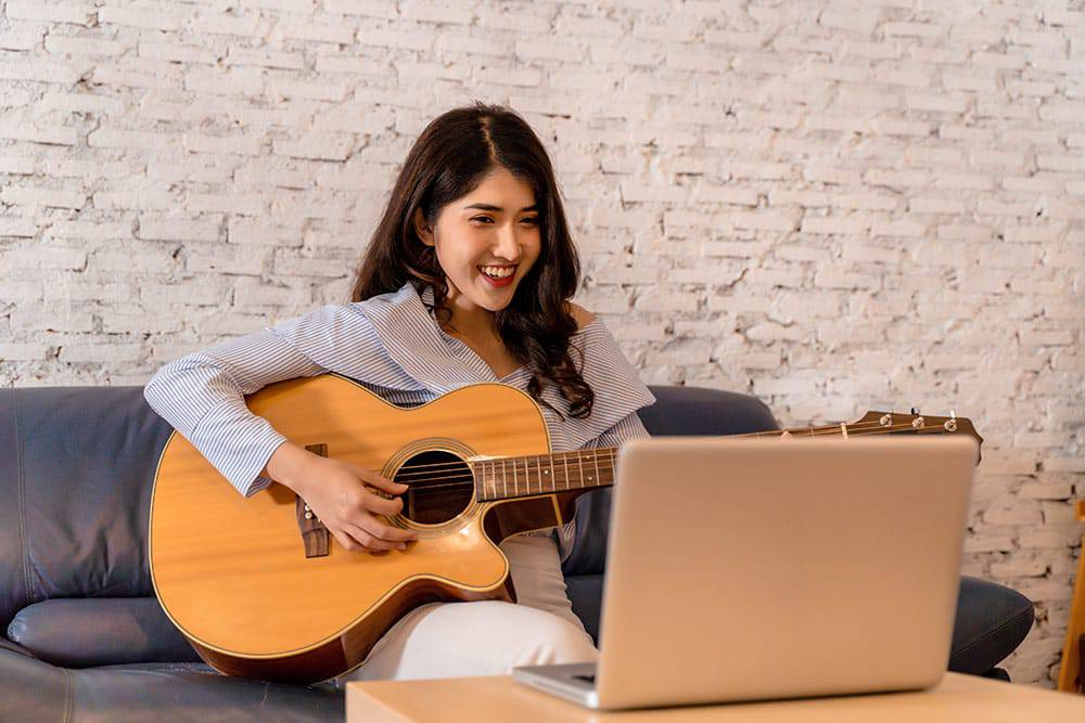 Young woman playing guitar in front of laptop sitting on couch
