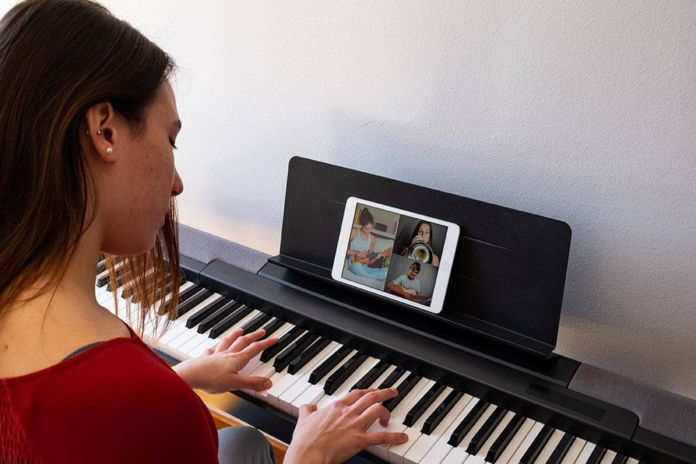 Woman playing keyboard while video chatting with other musicians