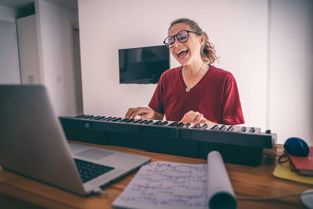 Woman playing keyboard on video call or private music lessons online