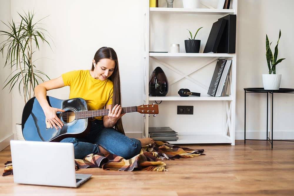Woman sitting on blanket on floor in front of laptop playing guitar, taking online music lessons