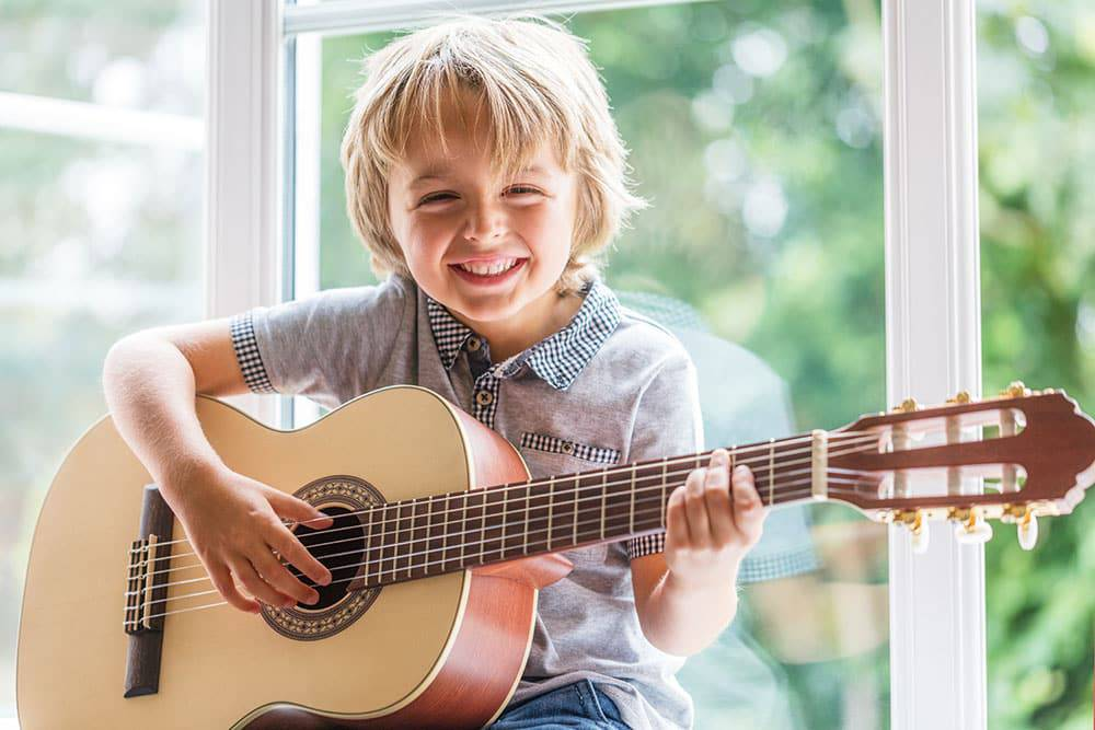 Young boy holding guitar smiling and happy sitting in front of window