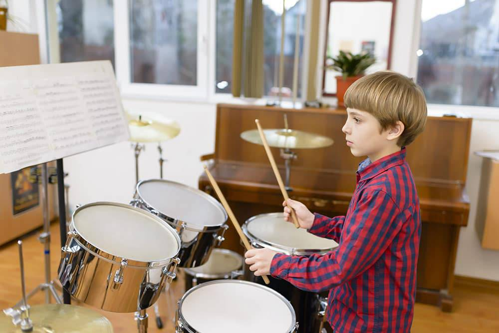 Young boy playing drums in classroom and reading music