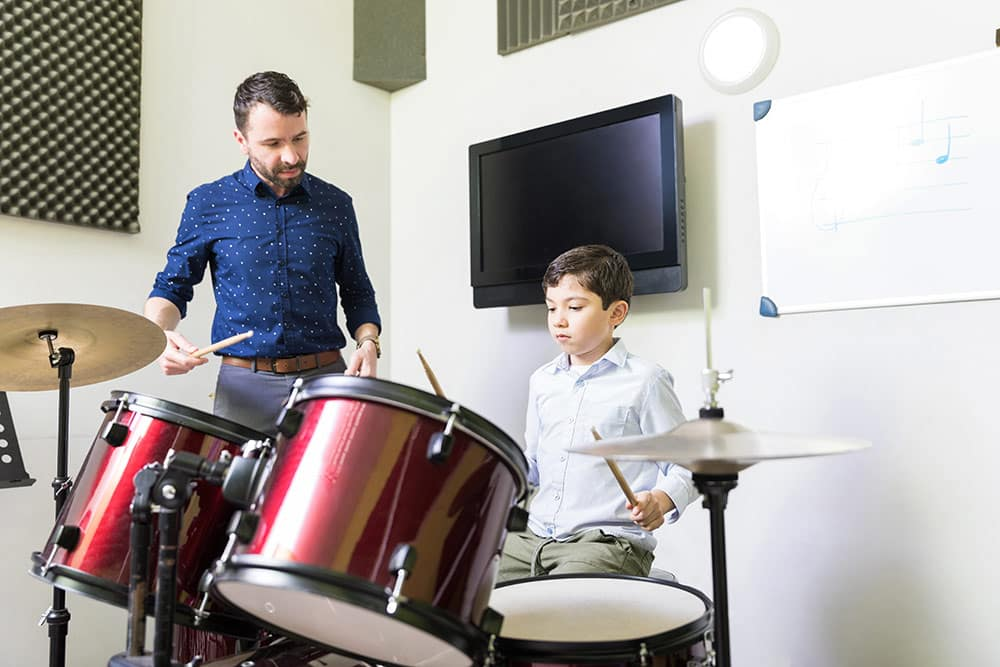 Young boy taking drum lessons with teacher