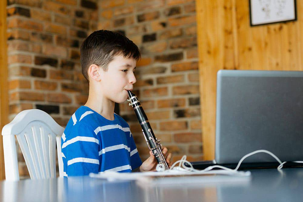 Young boy playing clarinet taking online music lessons