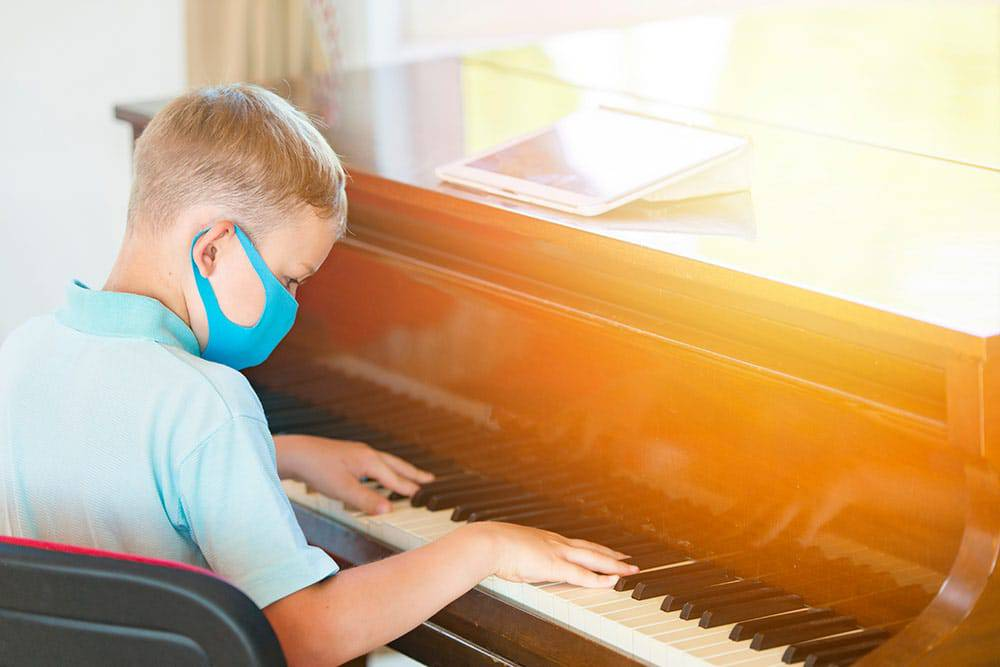 Young boy playing piano with blue face mask on