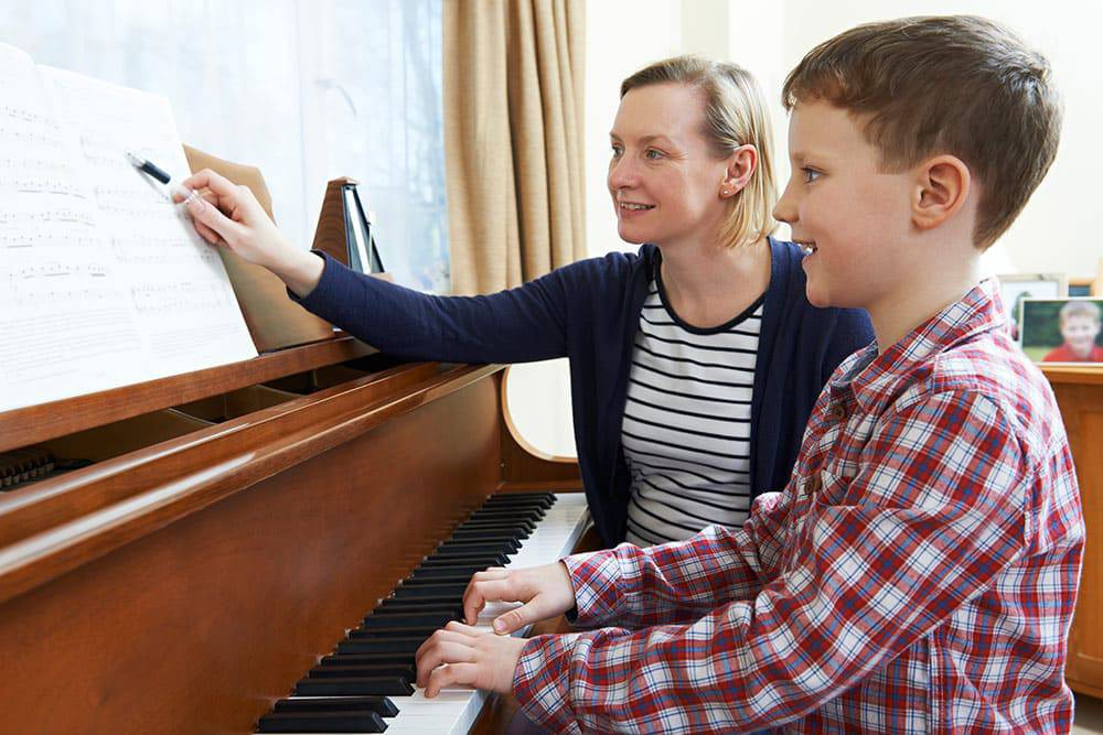 Young boy and teacher sitting on piano bench playing piano and reading music