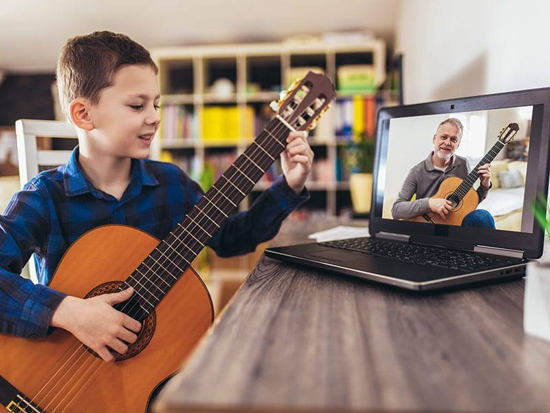 Young boywith guitar on laptop music class cover