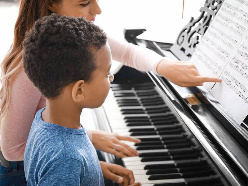 Young boywith instructor piano lessons cover