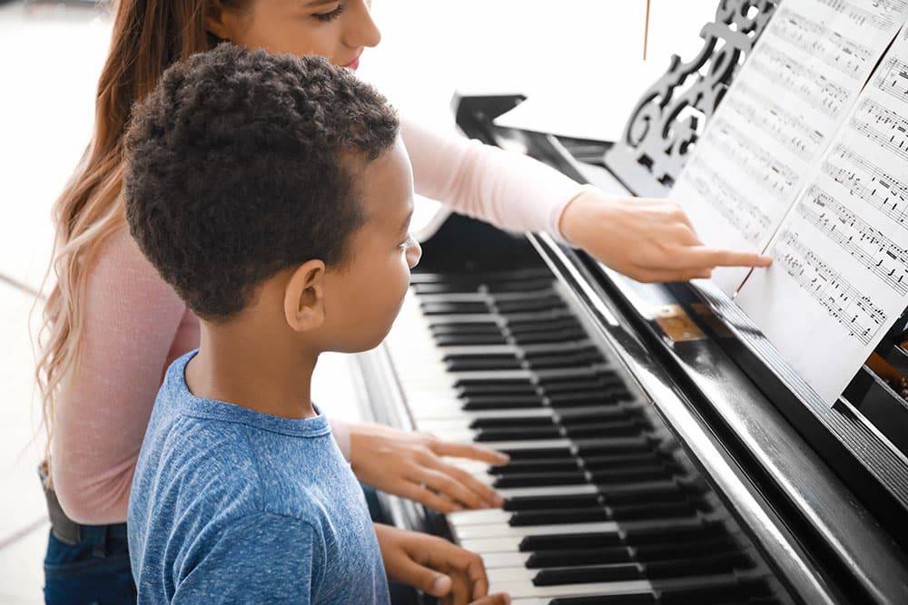 Young boy with teacher taking piano lessons