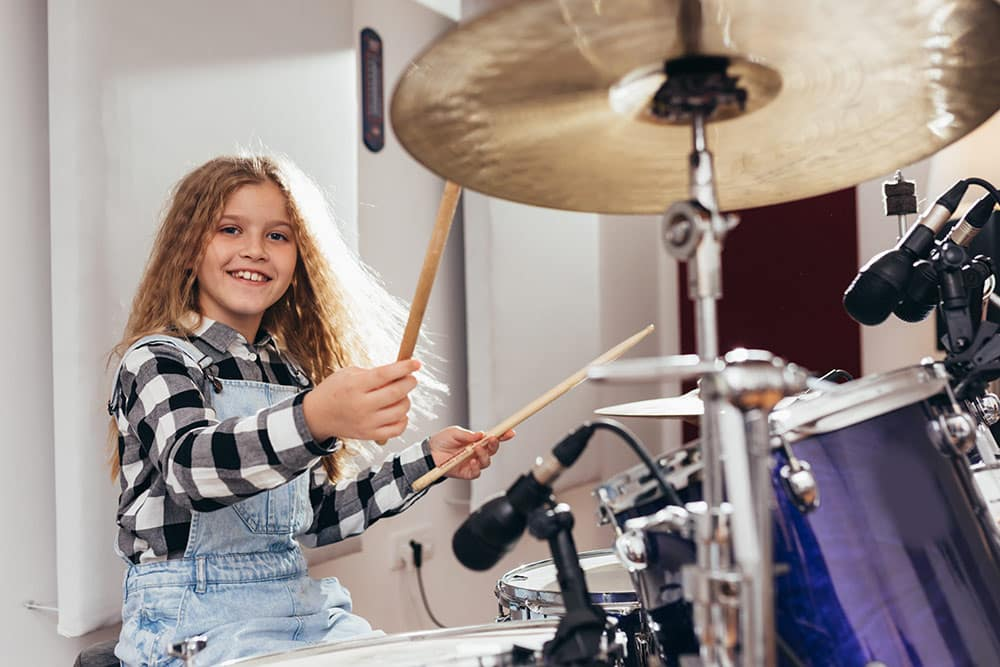 Young girl playing drums, having fun and smiling