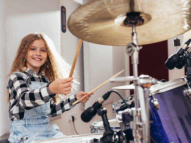 Young girl playing drums happyand smiling cover