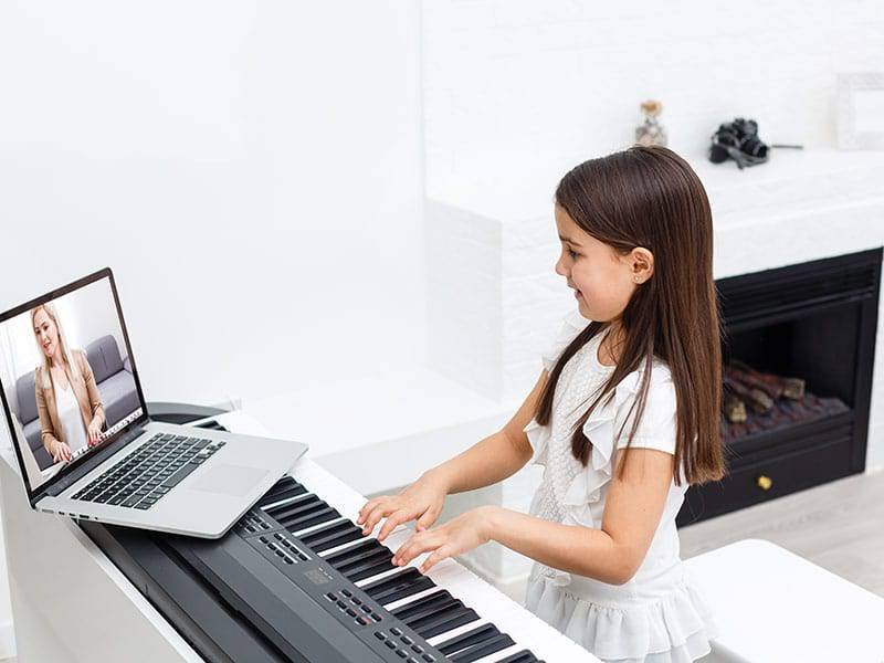 Young girl taking online music lessonsfor piano cover