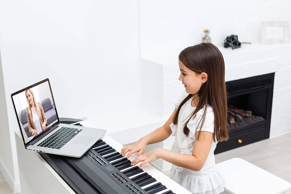 Young girl taking online music lessons for piano