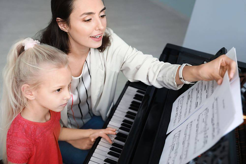 Young girl taking piano lessons with instructor