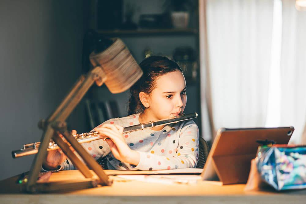 Young girl playing flute, looking at laptop on online music lessons