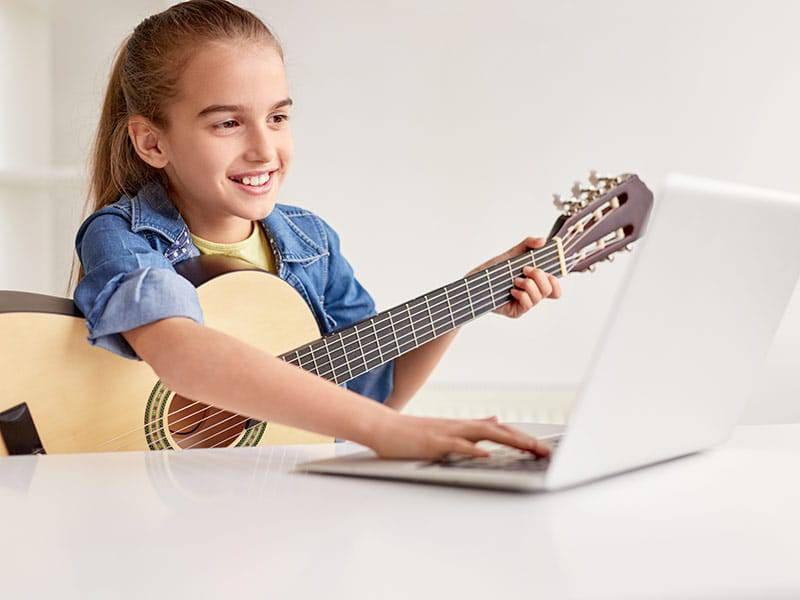 Young girlwith guitar taking online music lessons cover