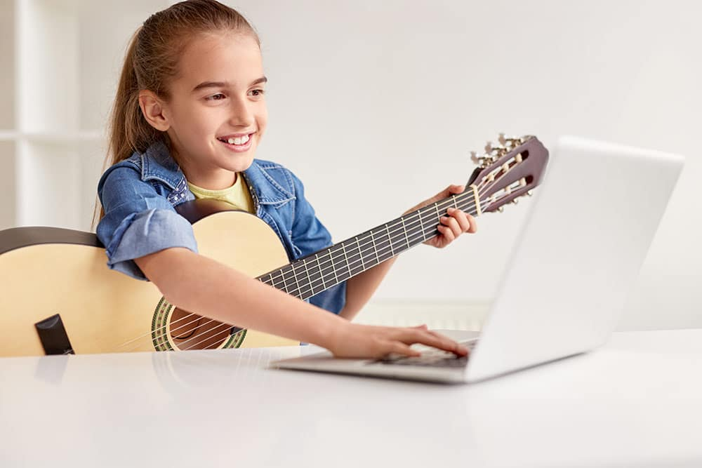 Young girl with guitar looking at laptop taking online music lessons