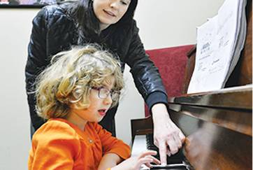 student and teacher in a piano lesson